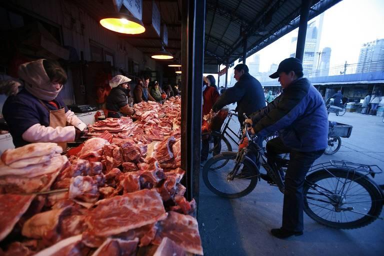Comerciantes vendem carne suína em barracas na rua na China