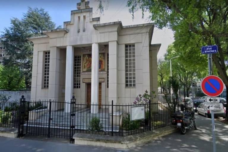 Fachada de uma igreja pequena, com duas colunas na frente e vitral na frente