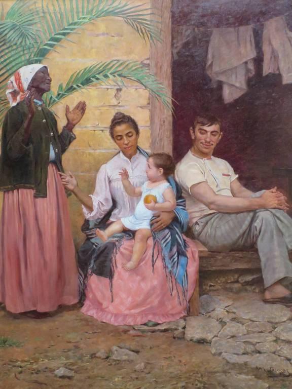 Da esquerda para a direita, pessoa negra em pé, mulher morena sentada com criança branca no colo e homem também branco sentado com a perna cruzada e a mão sobre o joelho