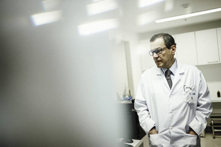 Médico com as mãos no bolso olha para o lado. Parte da foto é embaçada