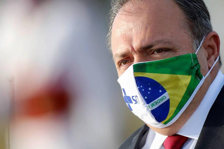 pazuello veste máscara com estampa metade bandeira do brasil metade logo do SUS