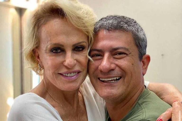 Ana Maria Braga e Tom Veiga estão abraçados e olham para a foto