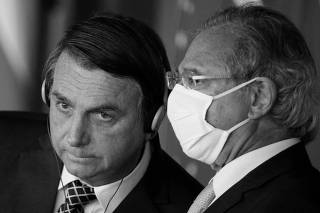Brazil's President Jair Bolsonaro listens to Brazil's Economy Minister Paulo Guedes during a statement to the media at the Itamaraty Palace in Brasilia