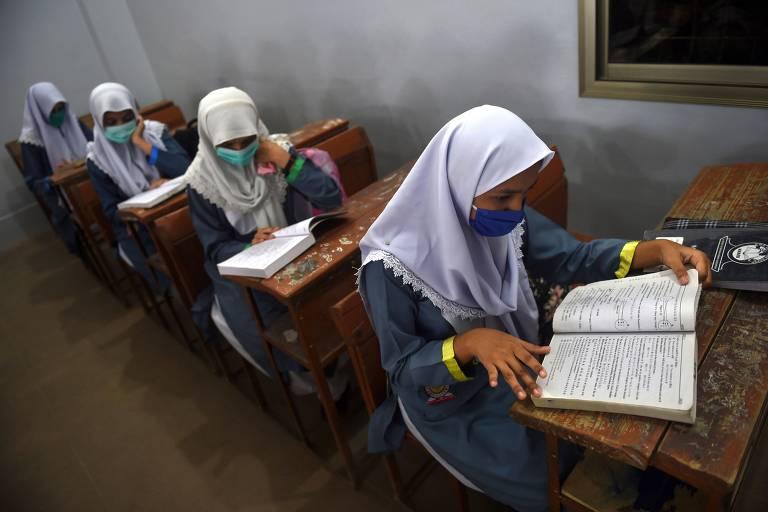 Estudantes usam máscaras durante aula em uma escola em Karachi, Paquistão