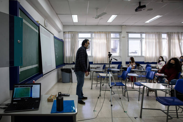 Marcelo Barão, professor de Física, dá aula ao mesmo tempo para alunos em sala e em casa