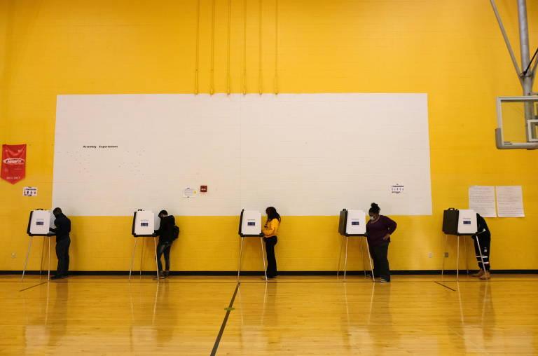Pessoas votando em cabines, vistas de longe, em parede amarela