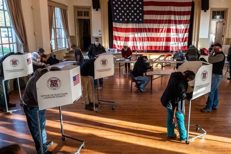 Pessoas em sala, abaixadas em cabines de votação