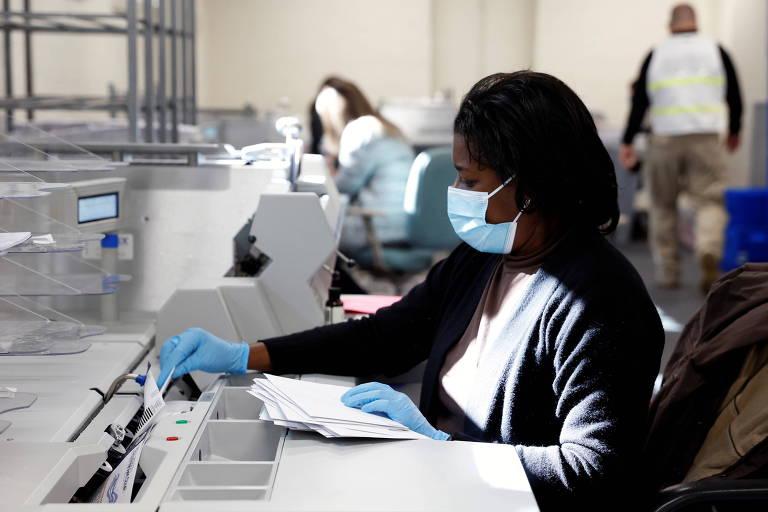Mulher negra sentada, com máscara, conta papéis em máquina