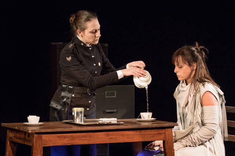 """Uma atriz serve café para outra atriz em cena do espetáculo """"Fronteira"""""""