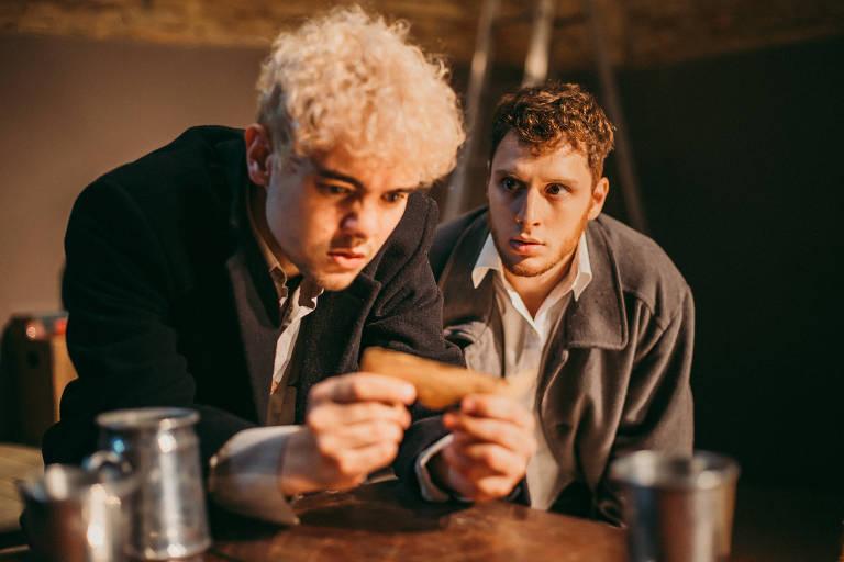 """Os atores Luccas Papp e Diego Martins olham para um bilhete durante o espetáculo """"O Estranho Atrás da Porta"""""""