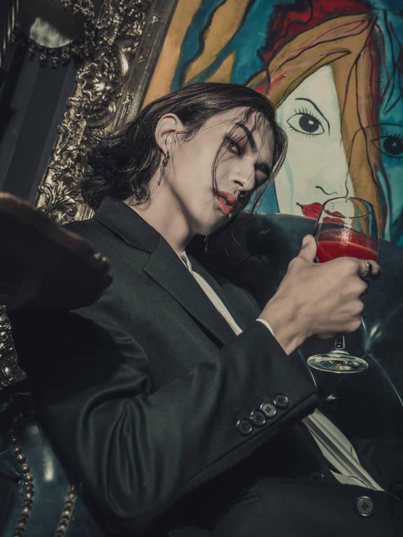 Homem de terno em primeiro plano, com parede grafitada atrás. Ele segura um copo com bebida na cor vermelha.