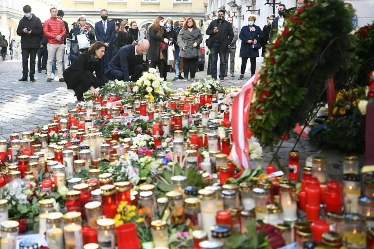 em primeiro plano centenas de velas e flores numa rua,  e ao fundo duas pessoas, uma mulher e um homem, de roupas escuras, agachadas colocando flores, observadas por pessoas em pé