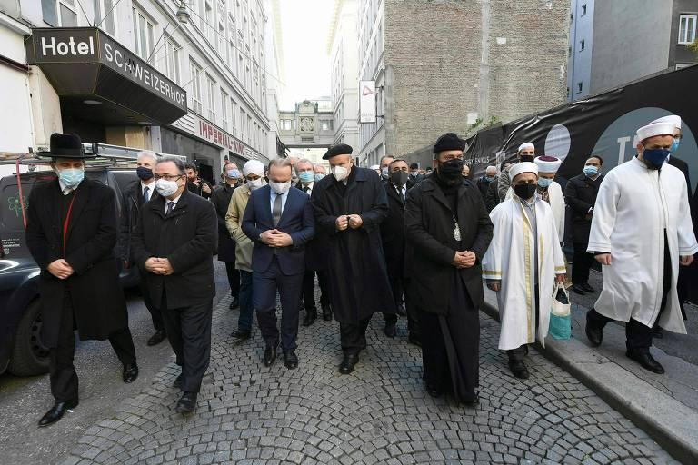 Vários homens de roupas pretas, e dois com roupas brancas de estilo árabe, andam em rua