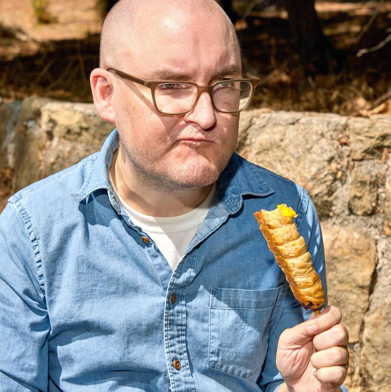 Homem branco careca come salgado no espeto