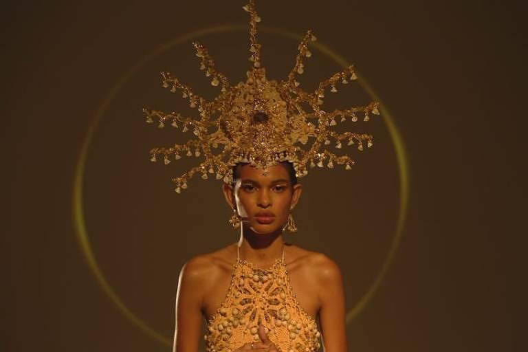 Mulher negra veste roupas douradas e coroa também dourada