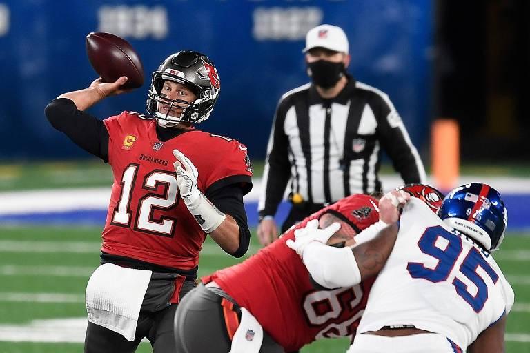 Tom Brady prepara um lançamento, enquanto seu companheiro de time bloqueia um rival