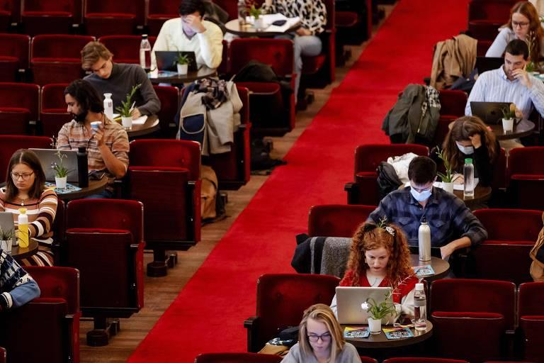 corredor com tapete vermelho entre fileiras de poltronas em auditório,com adolescentes sentados usando computadores