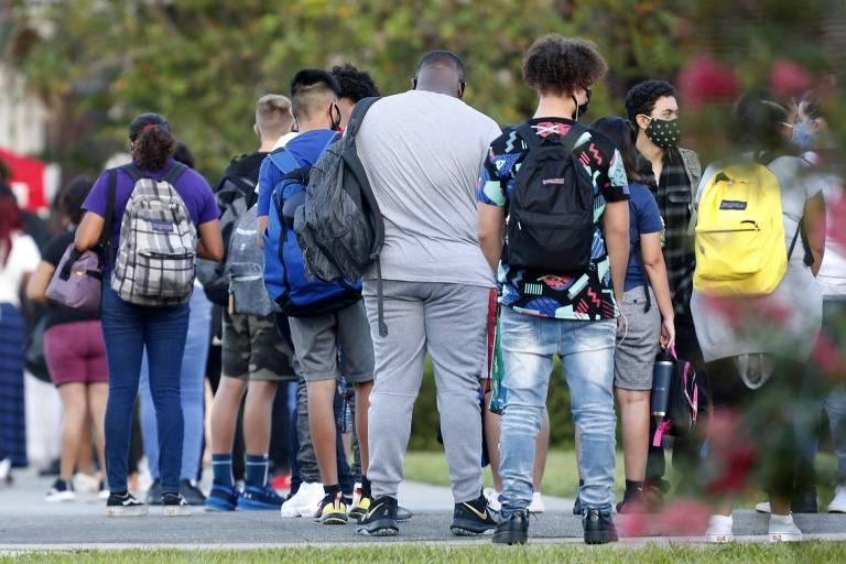 Fila de estudantes vistos de costas, alguns visivelmente acima do peso