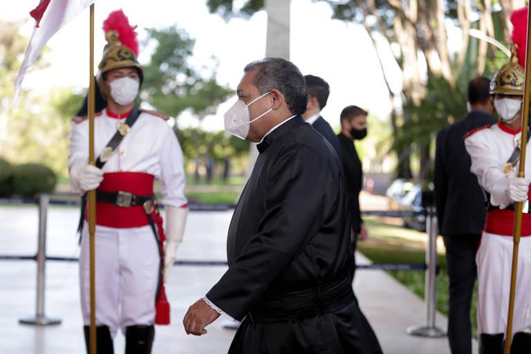 Um homem de máscara passando diante de guardas