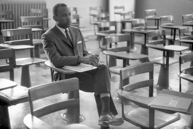 Homem negro, de terno e gravata, sentado em carteira escolar