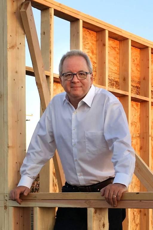 Retrato de Brian Fies, um homem cheinho, grisalho, de óculos; ele veste camisa branca e está numa casa em construção, é uma obra de madeira