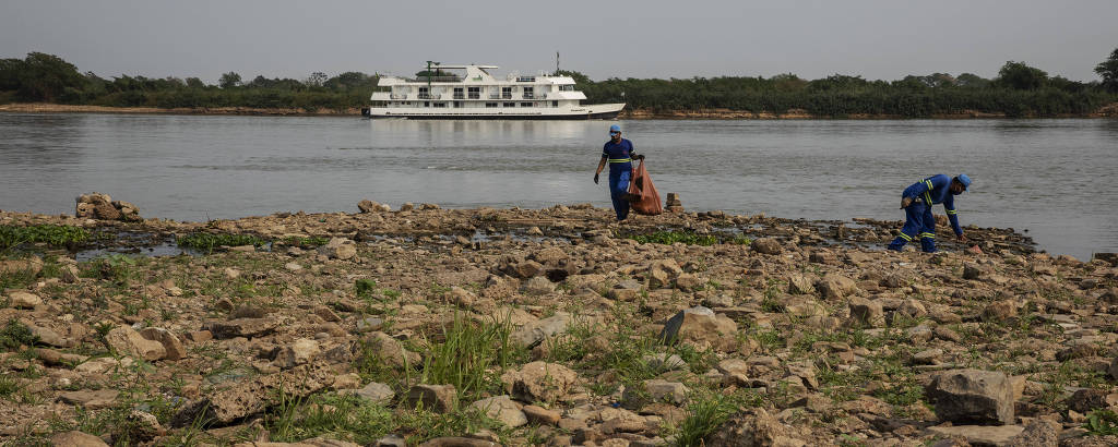 Garis limpam as margens do rio Paraguai na orla de Corumbá, em Mato Grosso do Sul