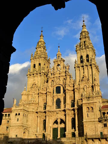 Cathedral with sunset light, view from Town Hall arch. Obradoiro Square, rainy day, grey sky. Baroque facade and towers, Santiago de Compostela, Spain.