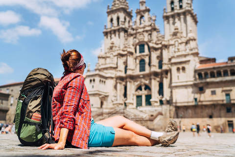 Young female backpacker piligrim sitting on the Obradeiro square (plaza) in Santiago de Compostela