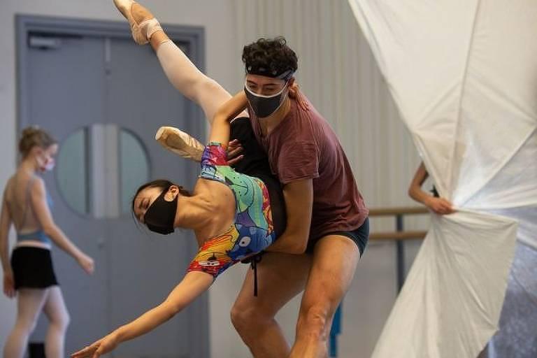 Os bailarinos ensaiam em pequenos grupos, usando máscaras