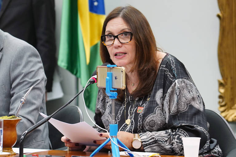 A deputada Bia Kicis, de cabelo solto, óculos e bata estampada branca e preta, segura papel e fala ao microfone sentada, apoiando os braços em uma mesa