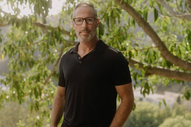 Homem branco de óculos ao lado de árvore
