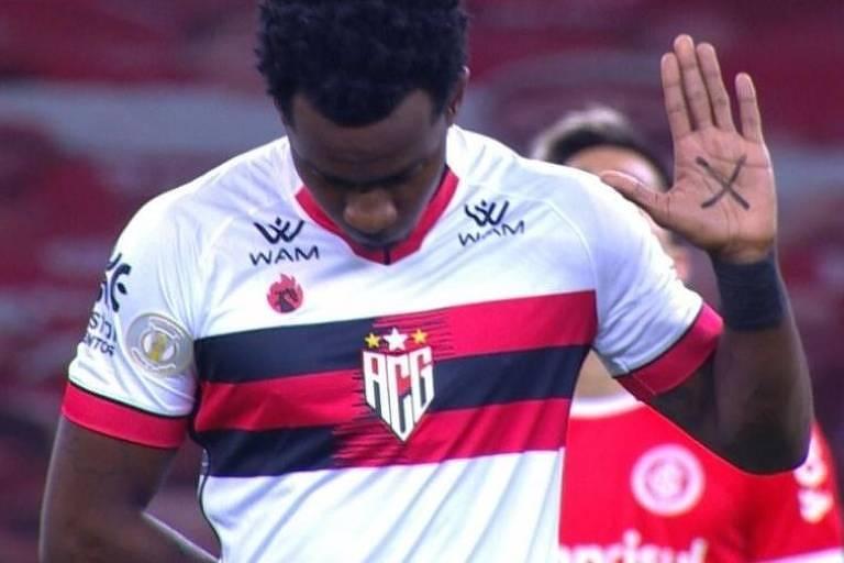 Hyuri jogador do Atlético-GO, mostra o X na palma de sua mão durante jogo contra o Inter, pela Copa do Brasil