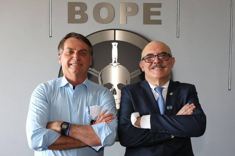 Bolsonaro e Milton Ribeiro de braços cruzados diante do símbolo do Bope, com facas em uma caveira