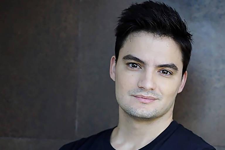 Felipe Neto é branco, sem barba, cabelo preto penteado para cima; ele está à direita da foto, é visto do pescoço para cima e e olha em direção à câmara