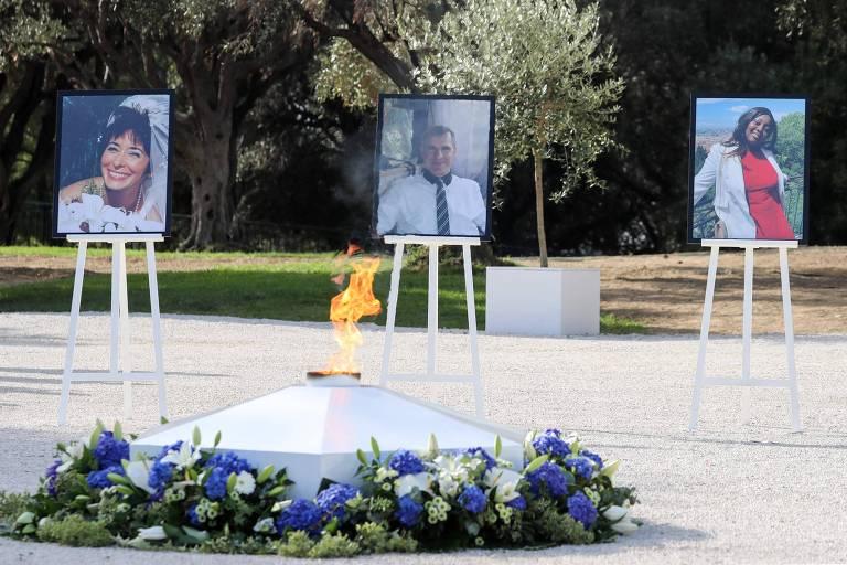Retratos de Nadine Devillers, Vincent Loques e Simone Barreto Silva, que morreram após ataque à faca na basílica de Nice, estão dispostos em frente a uma chama cercada de flores.