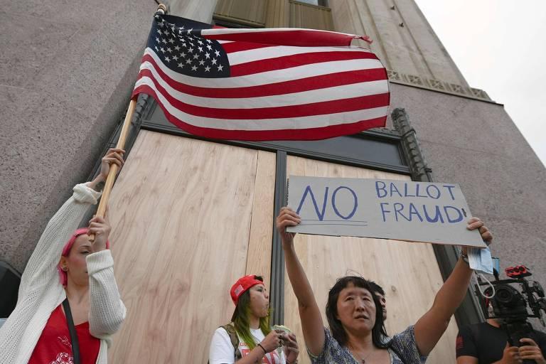 """Manifestante pró-Trump segura cartaz protestando contra """"fraude nas cédulas eleitorais"""" em Los Angeles, dia 6 de novembro."""