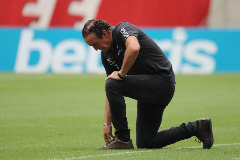 Cuca ajoelha no gramado durante jogo do Santos contra o Fluminense, pelo Brasileiro