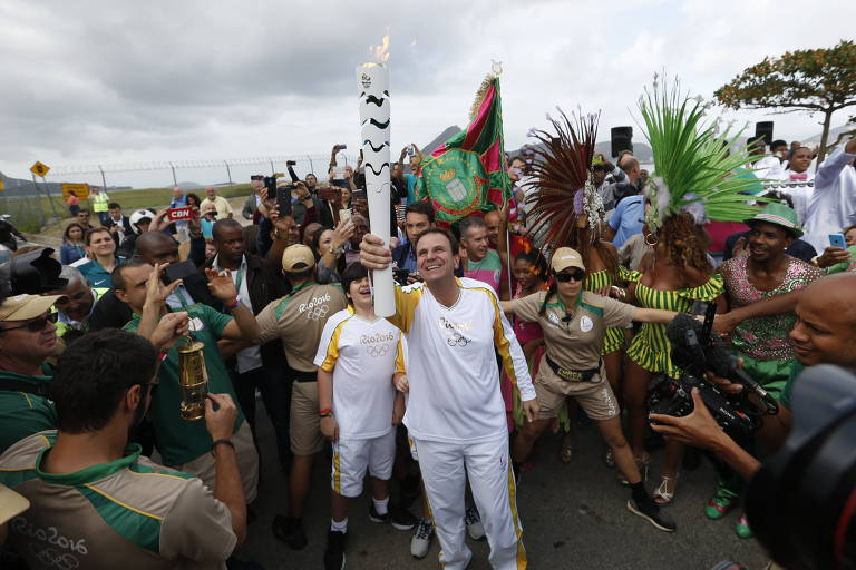 O então prefeito Eduardo Paes recebe a tocha olímpica no Rio de Janeiro, em 2016