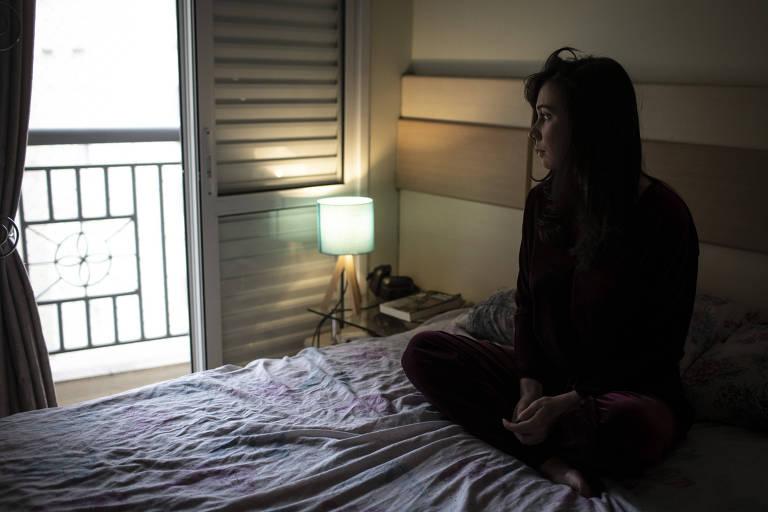 Heloisa está sentada na cama, em seu quarto, olhando para longe da câmera, na direção da janela. Seu rosto tem uma expressão séria