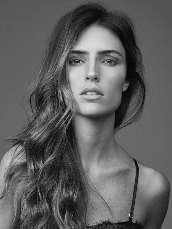 Foto em preto e branco da modelo Jessica Aronis. Ela olha para a câmera com o rosto sério, com os cabelos escorrendo sobre o ombro direito