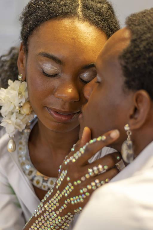 Duas mulheres negras com rostos próximos um ao outro e com strass no corpo