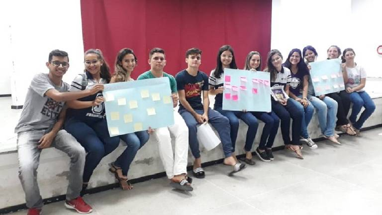 Vitória Cristina (6º à esq. segurando o cartaz) participa de uma reunião de mentoria com outros alunos em 2019, antes da pandemia do novo coronavírus