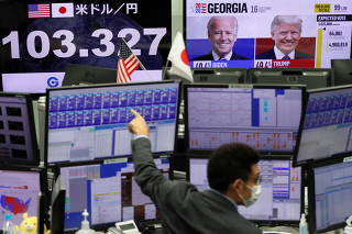 An employee of the foreign exchange trading company works in front of monitors showing the Japanese yen exchange rate against the U.S. dollar and news on the U.S. presidential election at a dealing room in Tokyo