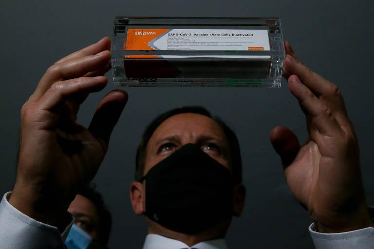 O governador Doria segura uma dose da vacina chinesa Coronavac durante visita a Brasília