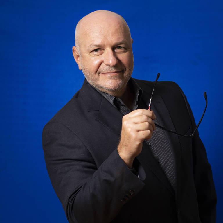 Milton Beck está de terno preto, segurando os ósculos com a mão direta, em frente a um fundo azul