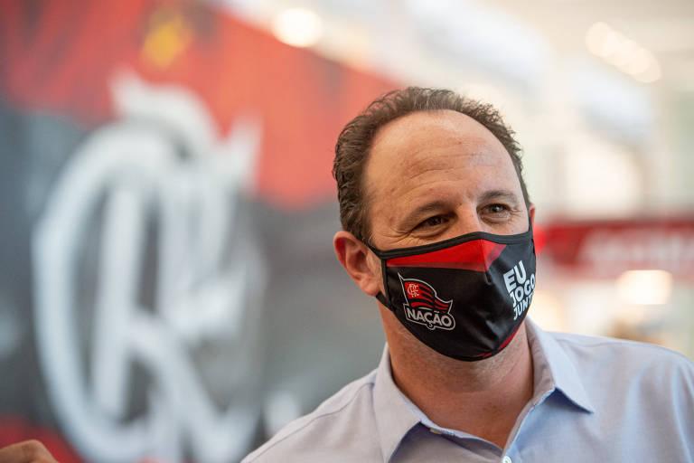 Ceni com máscara rubro-negra em frente a uma parede com símbolo do Flamengo