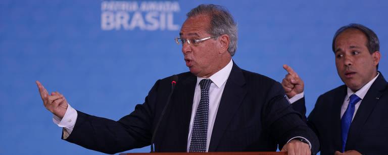 Paulo Guedes gesticula em um púlpito; ao lado direito, um tradutor de libras reproduz o discurso