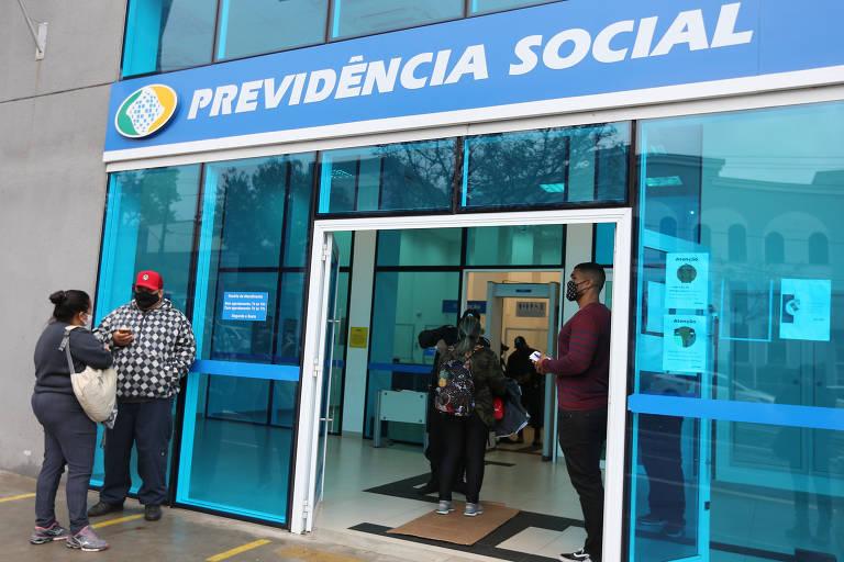 Pessoas estão em pé na entrada de agência do INSS na zona sul de São Paulo