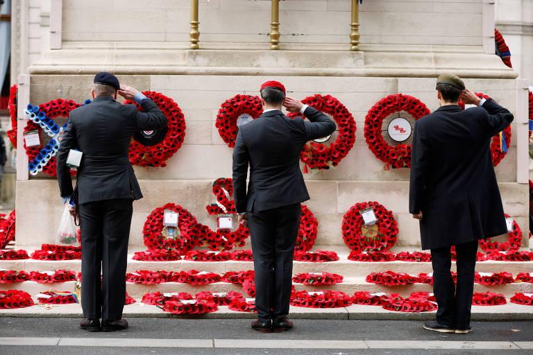 três homens fardados, de costas para a câmera, prestam continência a memorial com várias coroas de papoulas vermelhas, símbolos do armistício