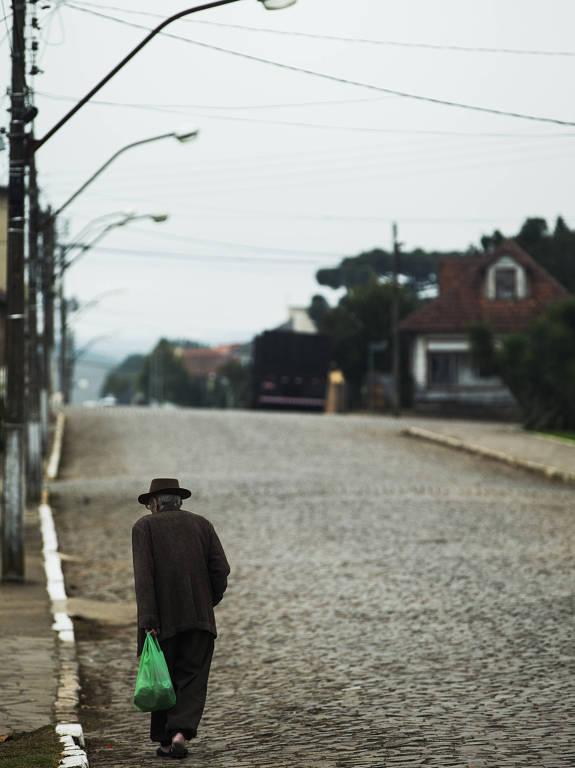 homem idoso e baixo, de costas, caminha sozinho por uma rua larga de paralelepípedos, em um dia nublado. ele veste um casaco largo e marrom e uma cartola da mesma cor